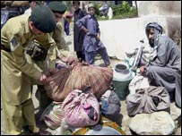 Pakistani troops check the belongings of returning Afghan refugees
