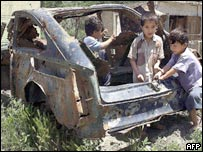 Boys play in a wrecked car in Kabul