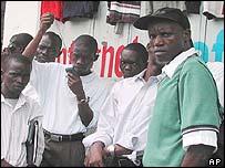 Residents in Monrovia gather round a radio to hear news