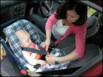 Mother strapping her child into a car seat