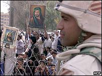 A US soldier watches a Shia protest in Baghdad