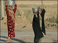 Iraqi women carry water in village near Baghdad