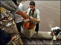 Iraqis fetch water from a damaged pipe