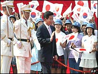 South Korean President Roh Moo-hyun, centre, accompanied by guards of honour, waves to Japanese school children