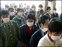 People wear masks as they wait for tickets at Beijing Railway Station