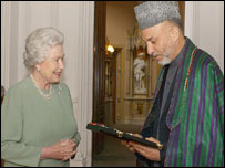 The Queen hands Mr Karzai his insignia