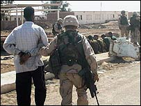 A US soldier leads away an Iraqi prisoner