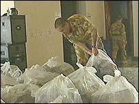 Soldier stacking bags of bank notes