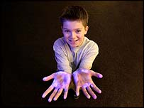 A child holds out his hands to show bacteria highlighted under UV light