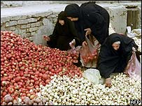 Iraqi women gather tomatoes and apples at a Baghdad street market