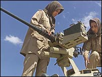 Female members of the Iraq-based People's Mujahideen guerrillas service a tanks at their base