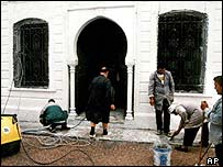Workers repaint the bomb-damaged synagogue