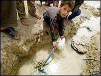A young boy fills his jug from a tapped city water pipe on the outskirts of Basra