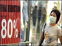A masked Singapore shopper walks past a 'sale' sign