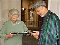 The Queen presents Hamid Karzai with the insignia of the Knight Grand Cross of the order of St Michael and St George