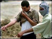 Iraqi men cover their noses against the stench as they find bodies at the Abu Ghraib Prison, outside Baghdad