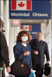 A passenger wears a face mask, while waiting for a shuttle outside Toronto's Pearson International Airport