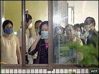 Family members of patients being treated at Taipei's Municipal Hoping Hospital try to call for help after they are barred from leaving the facility, 24 April, 2003.