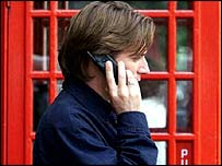 Man on mobile in front of phone box