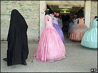 A woman in traditional Muslim robes passes party dresses in Hindia, Iraq