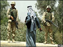 An Iraqi man walks past two US soldiers