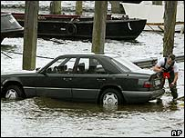 Man inspects flooded car in Hamburg, northern Germany