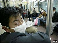 Masked passengers ride on the subway in Beijing, 25 April 2003