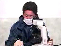 North Korean quarantine officer looks into a microscope (image: N Korean TV)