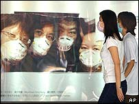 Hong Kong commuters wearing surgical masks walk past a poster promoting awareness of the need to take precautions against SARS