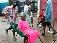 An old woman is carried in a wheelbarrow as fighting intensifies
