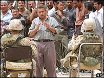 An Iraqi shopkeeper talks to US soldiers guarding the banking area of Baghdad