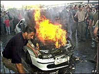Car burns after Wednesday's strike in Gaza City
