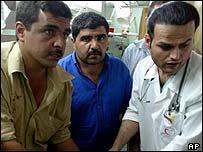 Relatives and medic treat Palestinian victim of rocket strike
