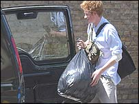Prince Harry carries his belongings to a car as he leaves Eton