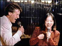Michael Palin and friend sing at a karaoke bar