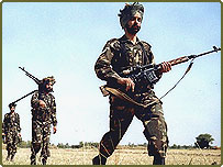 Armed Indian soldiers move in single file near Jammu, close to the border between India and Pakistan.
