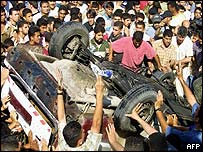 Palestinian crowd around wreckage of Yasser Taha's car