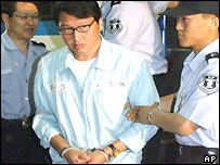 SK chairman Chey Tae-won is handcuffed as he enters the Seoul court