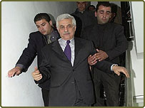 Palestinian Prime Minister Mahmoud Abbas flanked by security guards