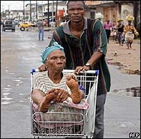 Man pushing a woman in a shopping trolley