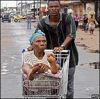 Man pushing a woman in a shopping trolley