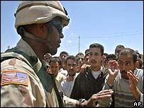 An American soldier tries to explain his side of the story to angry Iraqis