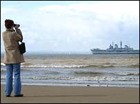 An onlooker watches HMS Invincible approach Liverpool