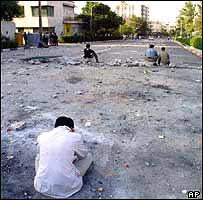 Students sit amid the debris of the clashes on Friday