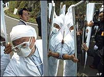 Suspected cult group members, all clad in white from head to toe, hold mirror-like shields as they face off with local police officers