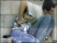 Muhammad al-Durrah, sheltered by his father, screams in panic during previous fighting in Gaza