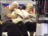Two elderly woman sleep as they wait for their flight at the deserted Ben-Gurion airport