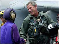 George W Bush shakes hands with a sailor after landing on the USS Abraham Lincoln