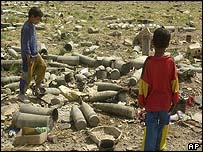 Boys walk through unexploded munitions in southeast Baghdad