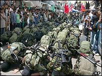 Hamas militants pray during the procession